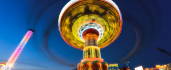 A blue hour long exposure landscape orientation wide angle photograph of Wave Swinger; a carnival swing captured in motion at Casino Pier, Seaside Heights, New Jersey.