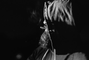 Ceramicist and potter, a hooded Jeff Ruemeli smokes the last of his cigarette as he stokes the soda kiln fires in this low key black and white portrait.