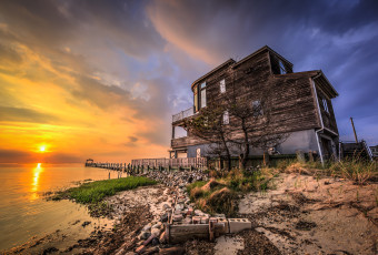 High drama at sunset befalls a lone house sitting along the bayfront of Little Egg Harbor in this HDR sunset photograph