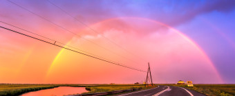 Photograph of a double rainbow arching over power lines and Dock Road at sunset
