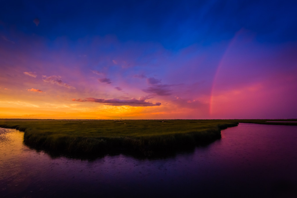 Photograph of stunning clouds, pastel skies and a rainbow appear over the marsh at sunset