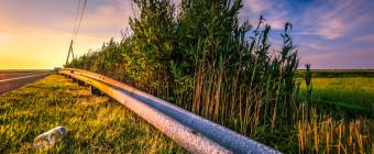 Golden hour photograph of guardrails, power lines, litter and the salt marsh