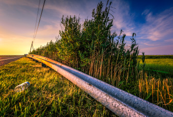Golden hour photograph of guardrails, power lines, litter and the salt marsh