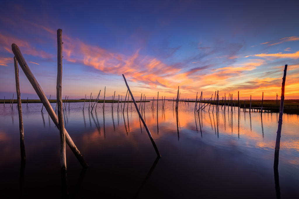 Wide angle HDR photograph of an abandoned marina and a reflective sunset on Great Bay