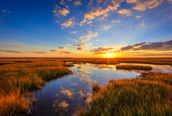 Wide angle HDR photograph of a vibrant golden hour over marsh