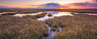 HDR landscape photograph taken at sunset over tide pools and marsh