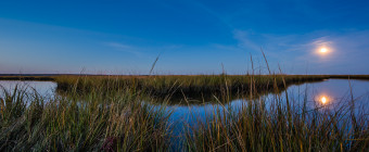 Wide angle landscape photograph of a Full Moon over marsh at blue hour