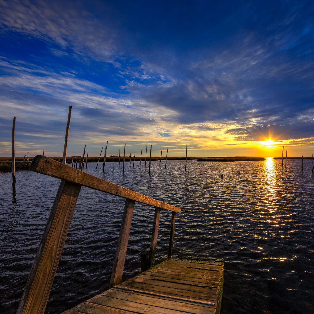Square format HDR landscape photograph of dock and bay at sunset