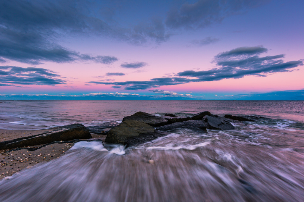 Wide angle photograph of ocean jetty rock captured at blue hour