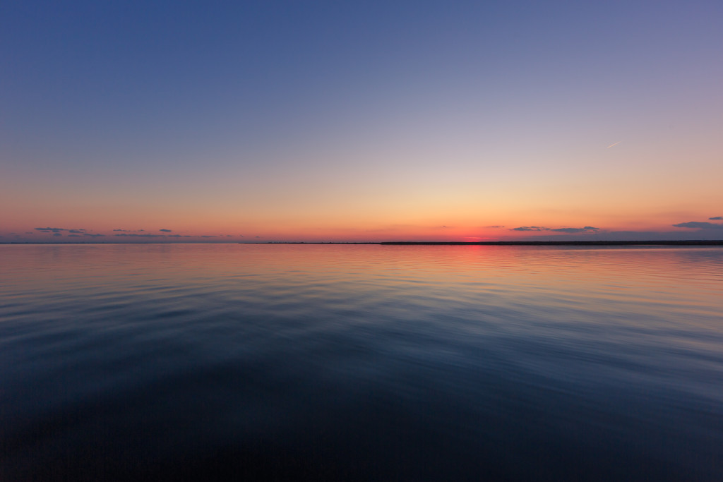 Wide angle landscape photograph of calm bay water and clear sky at blue hour