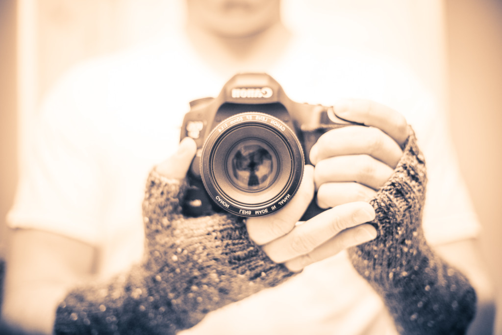 Shallow depth of field photograph modeling a canon body and hand knit fingerless gloves