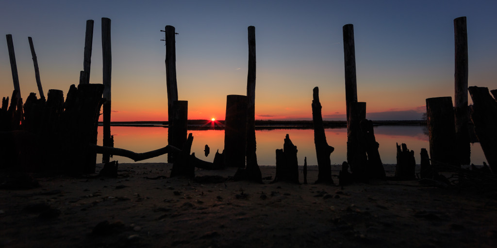 Wide angle landscape photograph of still water and silhouette dock remains at sunset