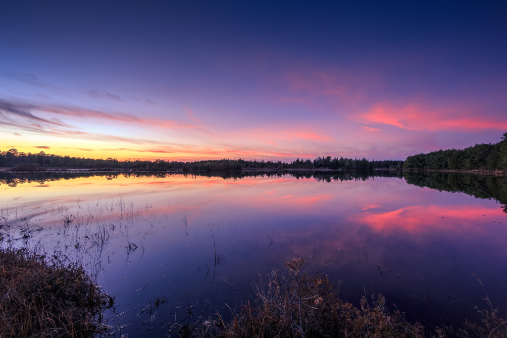 Wide angle HDR landscape photograph of a pastel color sunset over a mirrored lake at Stafford Forge
