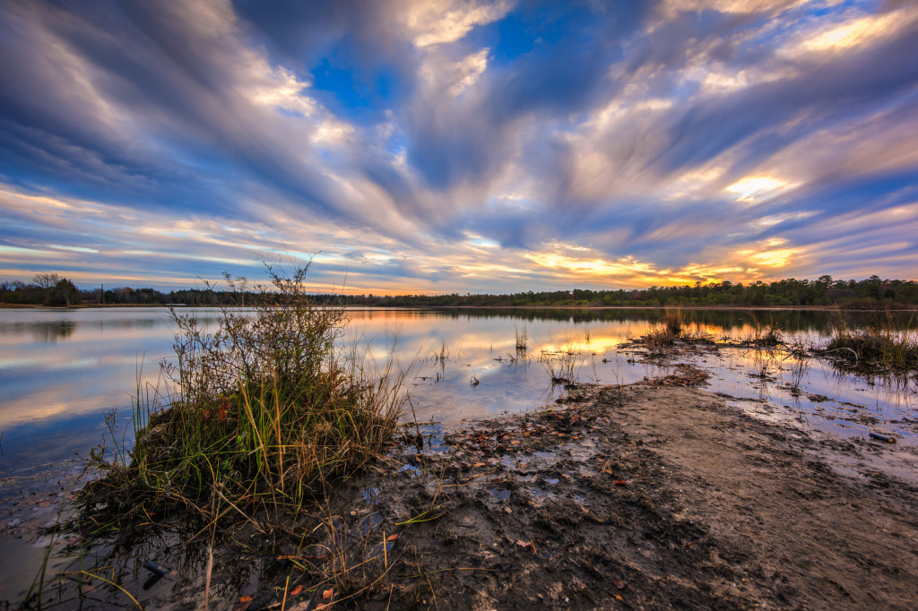 Wide angle landscape HDR photograph of wind swept clouds over still water at Stafford Forge