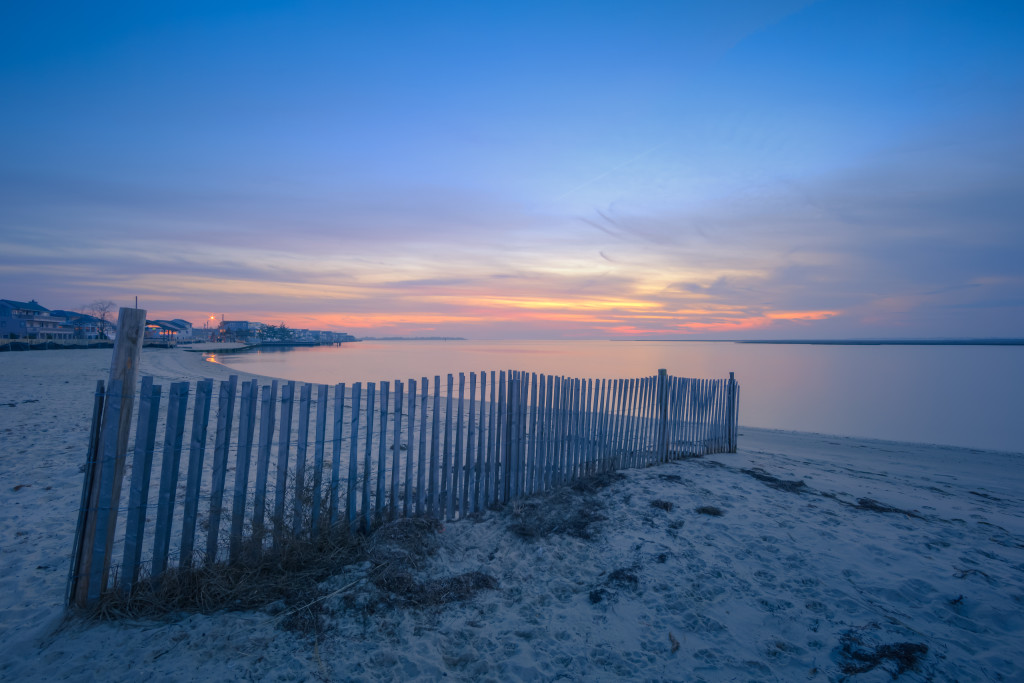 Blue hour HDR photograph overlooking dune fence and calm bay water
