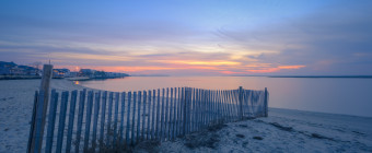 Blue hour HDR photograph overlooking dune fence and calm baywater