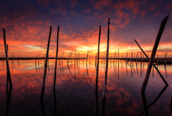 HDR photograph of a fiery sunset mirrored over reflective water