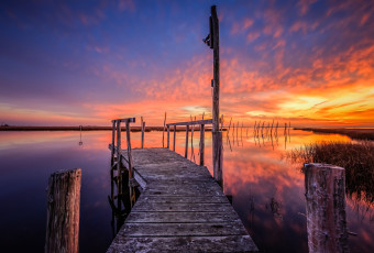 HDR photograph of an abandoned dock set afire by intense sunset color