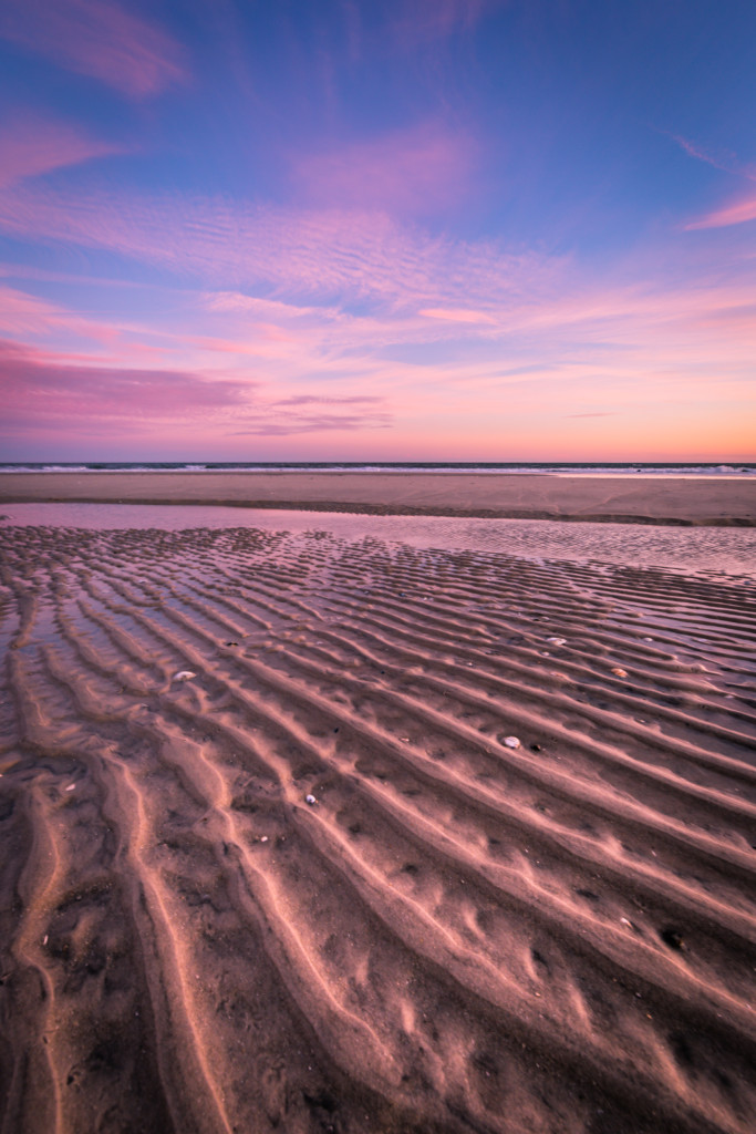 Vertical orientation photograph with strong leading lines in the sand underneath a pastel sunset