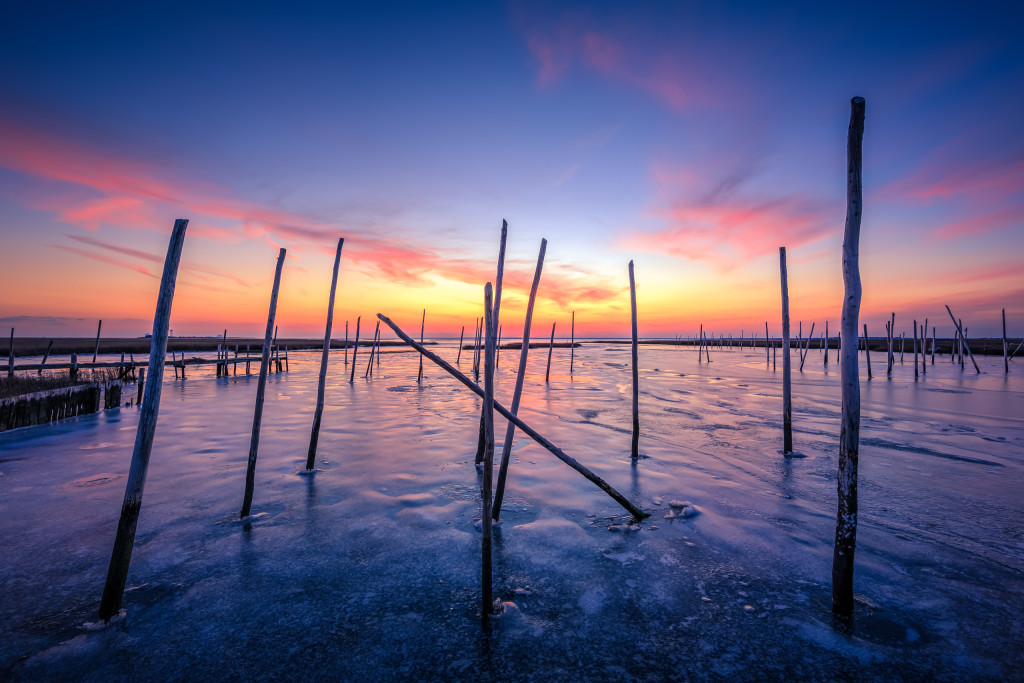 Sunset photograph of frozen bay ice locking in marina posts