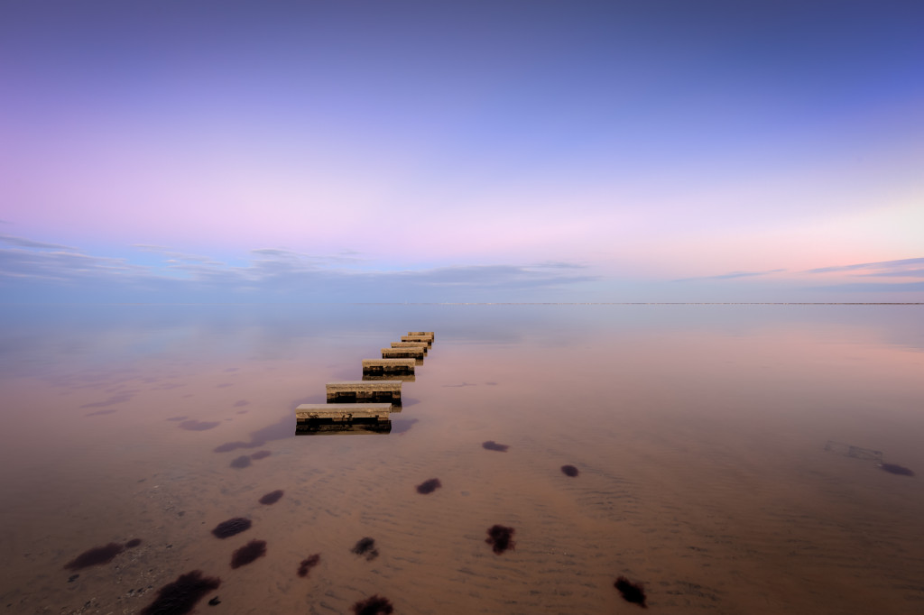 Blue hour photograph of an exposed manmade jetty in Barnegat Bay