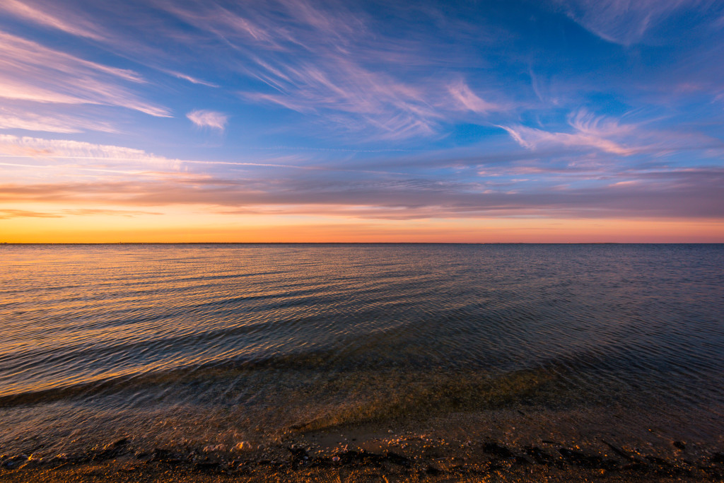 Landscape photograph of wispy clouds and a calm Barnegat Bay at sunset