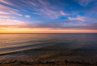 Landscape photograph of whispy clouds and a calm Barnegat Bay at sunset