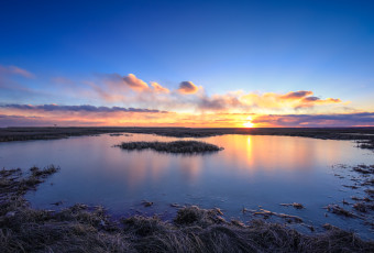 Sunset photograph of salt marsh just frozen over