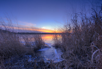 Blue hour photograph taken among marsh grass at a frozen Stafford Forge