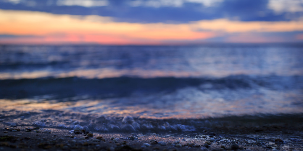 Shallow depth of field landscape sunset photo of small bay waves lapping on shore