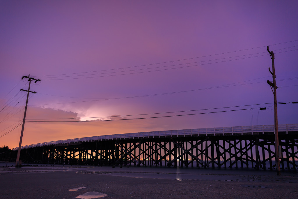 Long exposure photograph of Great Bay Boulevard's first bridge backlit by lightning.