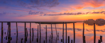 Sunset photo of layered pastel clouds, wood pilings, and a smooth water reflection