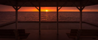 Sunset photograph from Surf City Sunset Park gazebo with sunlight casting a strong orange glow.