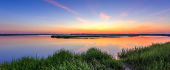 Sunset photograph of dead calm conditions highlighting vibrant green marsh grass just after sunset.