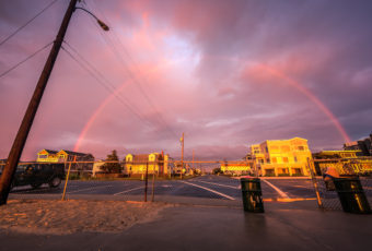 Wide angle HDR photograph of a rainbow forming over Long Beach Island houses bathed in gold.