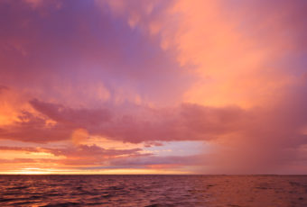 Vertical orientation sunset photograph of dramatic skies and rich pastels over Barnegat Bay.