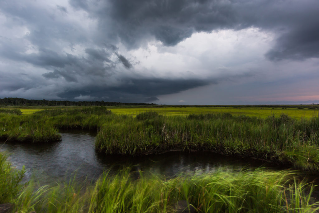Wide angle photograph of severe weather clouds moving in over a salt marsh.