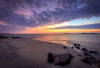 Sunset photo with pastel skies and a jetty rock foreground.