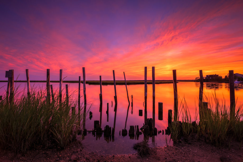 Fiery sunset ignites with stunning marsh tributary reflection.