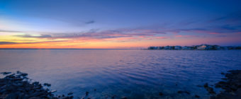 Blue hour photograph of jetty rock shore and Barnegat Bay from Harvey Cedars Sunset Park.