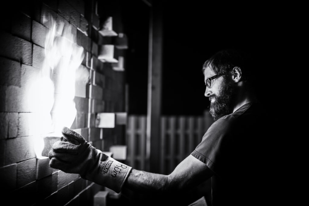 Black and white photograph of Jeff Ruemeli working a soda kiln.