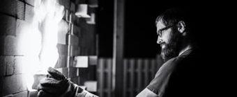 Black and white photograph of Jeff Ruemeli working a soda kiln.