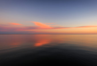 Motion blur sunset photo of pastel clouds and calm bay water.
