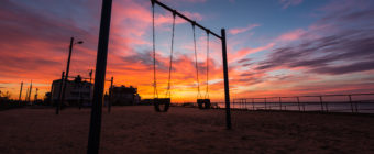 Fiery sunset photograph backlights park swings.