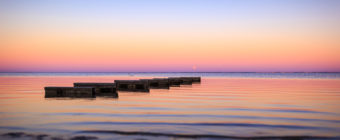 Sunset photo of a rising supermoon over gentle waves of Barnegat Bay.