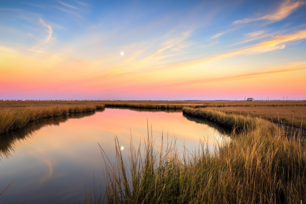 Sunset photo of a reflective moonrise over marsh amid pastel clouds.