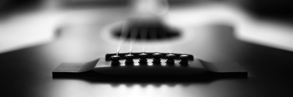 Black and white photo of acoustic guitar bridge.