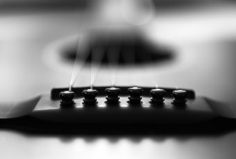 Black and white photo of acoustic guitar bridge.