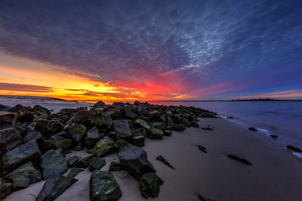 Bayside sunset photo over sand and jetty rock.