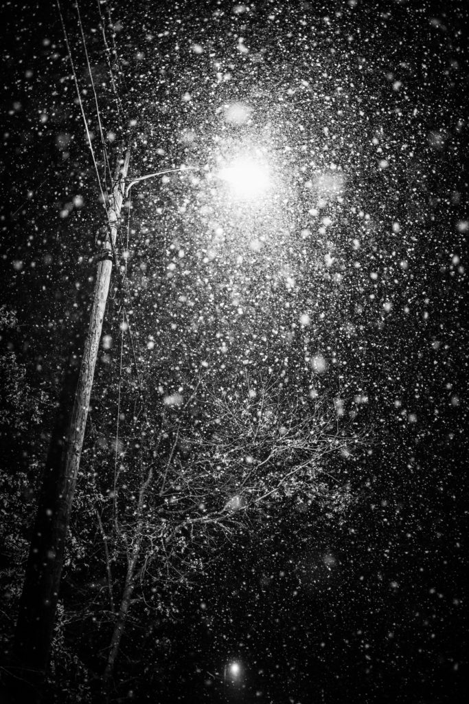 Low key black and white photo of heavy snow lit by streetlight.